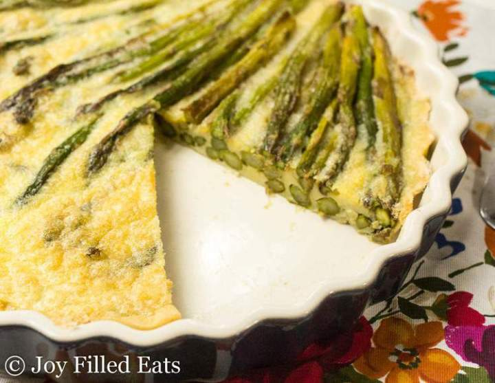 Large tart pan with an asparagus quiche with one slice missing