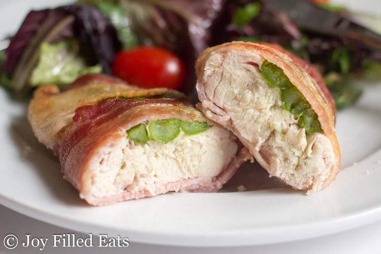 Stuffed Chicken with Asparagus Wrapped in Bacon cut in half on a white plate