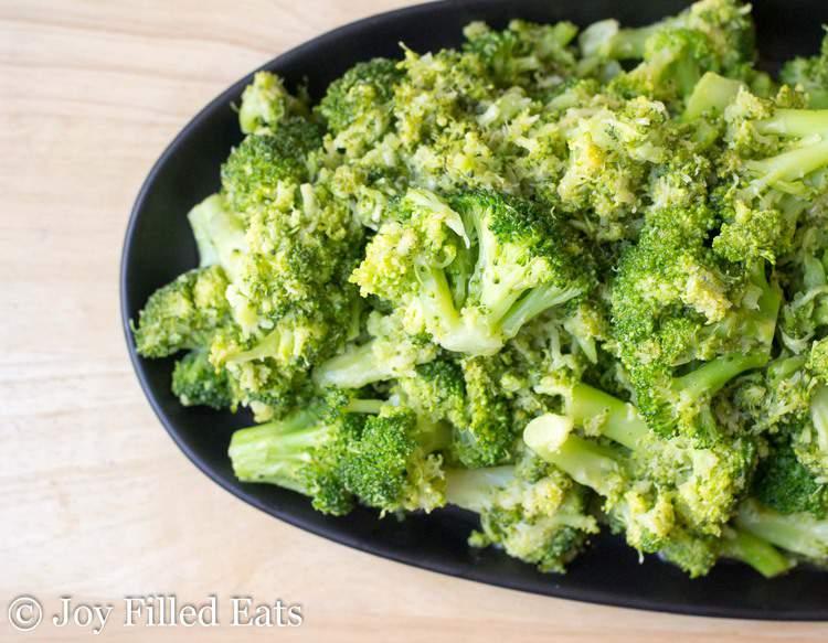 garlic broccoli on a black serving tray