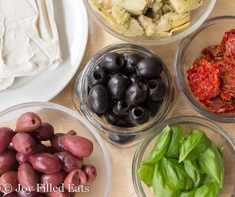 Small bowls of olives, artichokes, sundried tomatoes, basil, and cream cheese