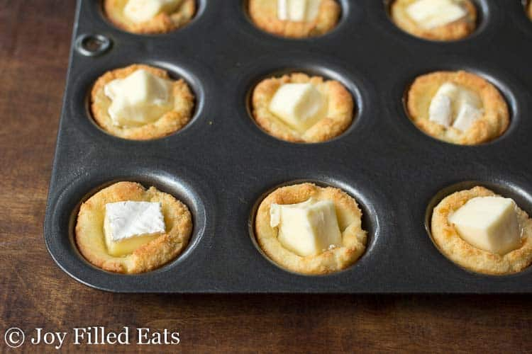 Cubes of brie cheese in the center of the baked dough cups in a mini muffin tin