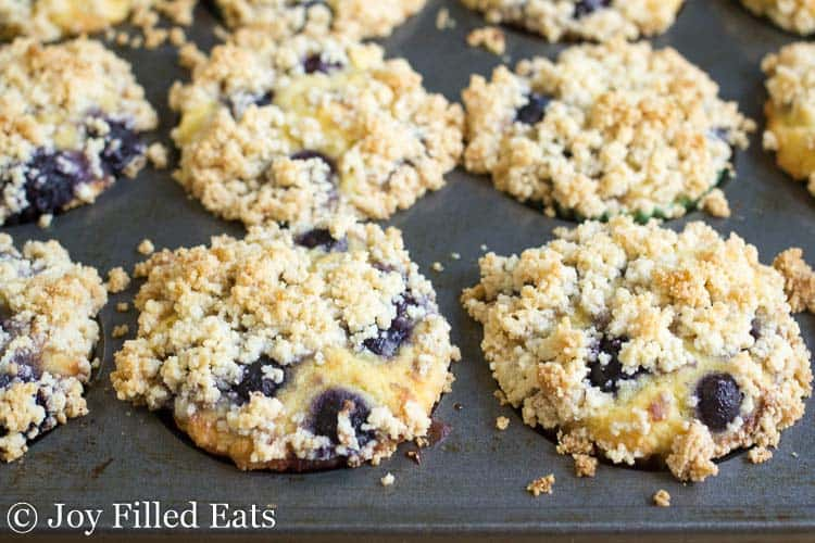 The muffin tin with the baked blueberry muffins with crumb topping