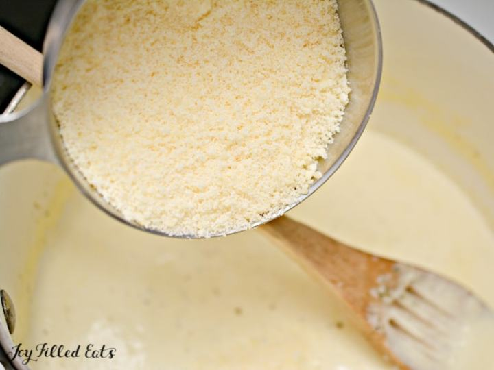 the cheese being added to the alfredo sauce in a large pot
