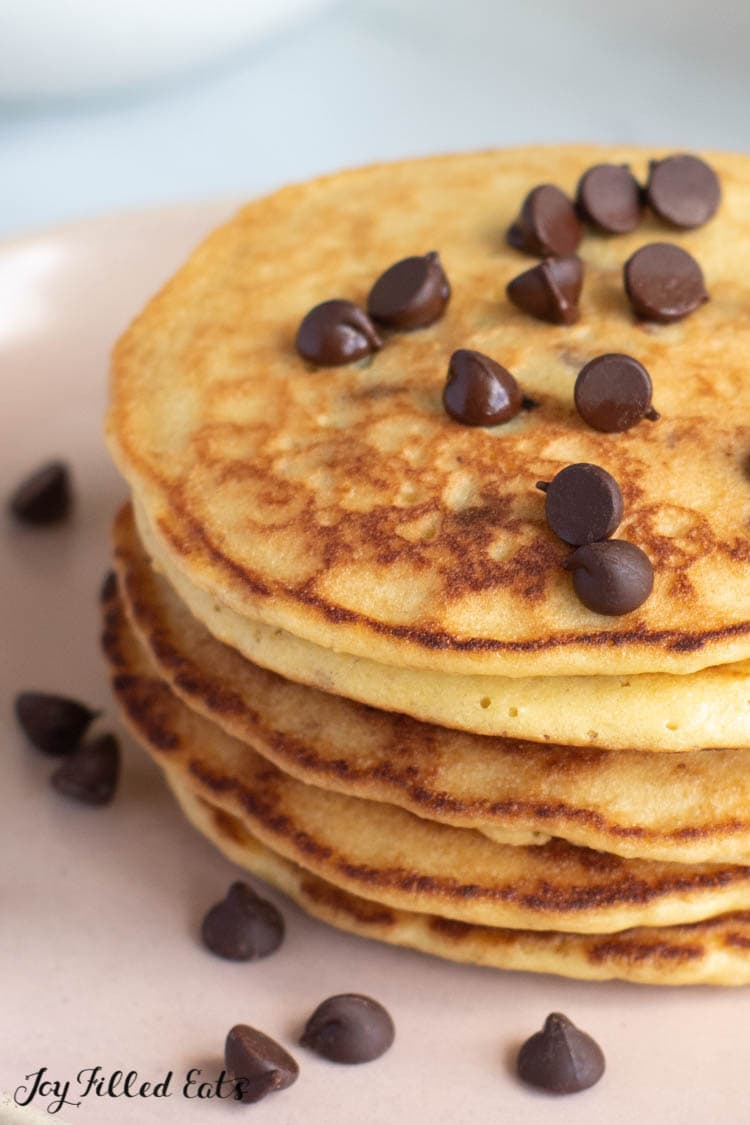 close up of a stack of almond flour pancakes with chocolate chips on a plate