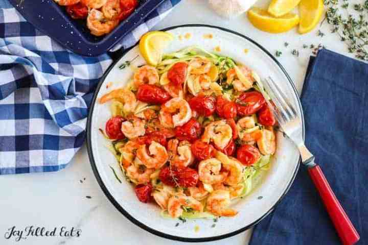 bowl with zucchini noodles topped with oven baked shrimp with garlic