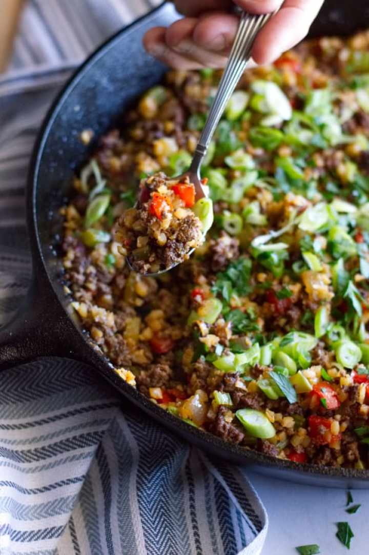 a spoon scooping some of the dirty keto cauliflower rice recipe out of the skillet