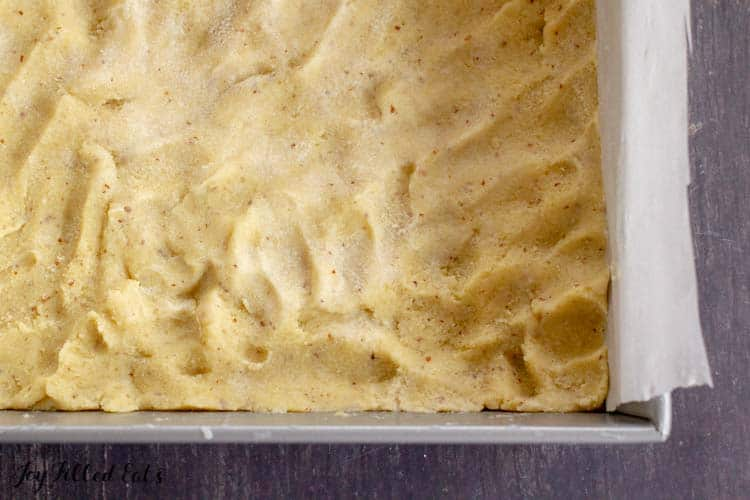 the healthy lemon bars crust pressed into the bottom of a parchment lined baking pan
