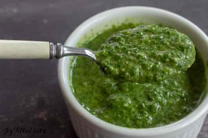 a spoon lifting up some pesto from a small bowl