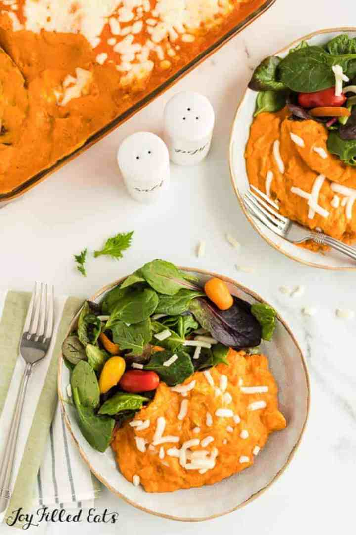 two plates with Spaghetti Squash Casserole with Chicken and pink sauce paired with a green salad