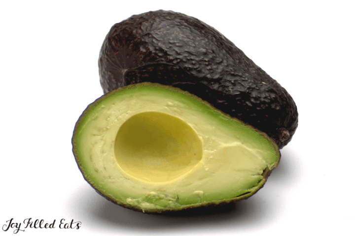 an avocado cut in half with the pit removed