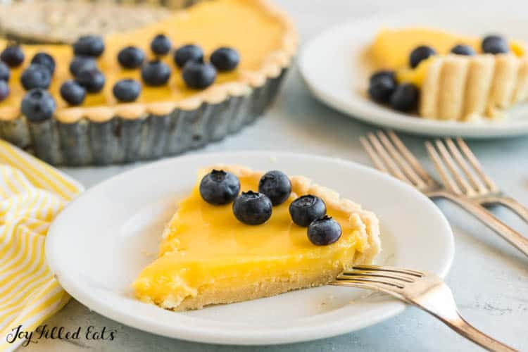 a slice of lemon curd tart on a white plate with blueberries