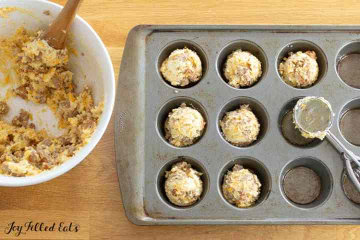 scoops of sausage muffin batter in a muffin tin