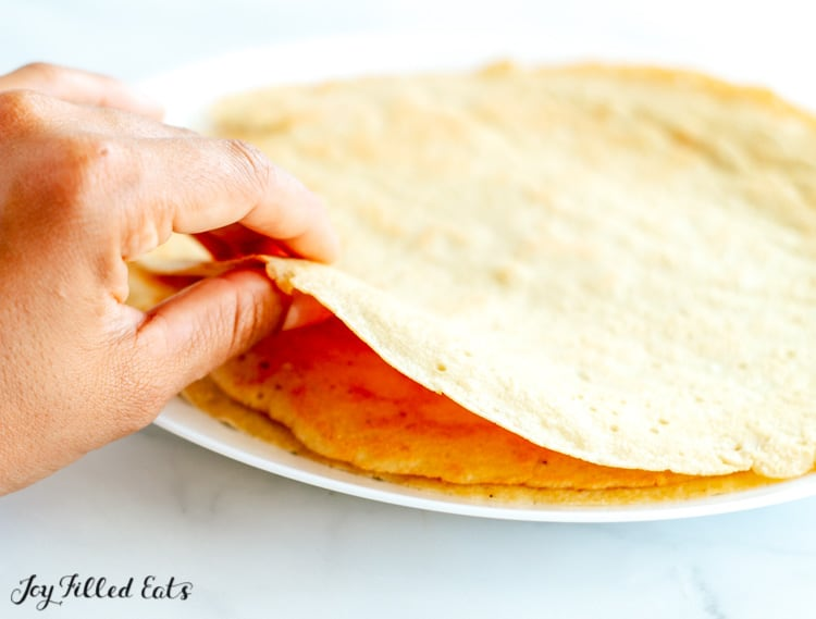 a hand lifting a crepe up from a stack to show the thickness