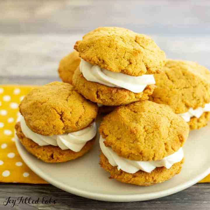 a stack of keto pumpkin cookies on a plate on top of a polka dot napkin