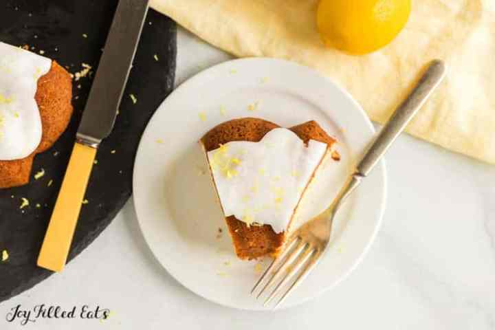 a slice of Lemon Drizzle Cake on a white plate with a fork