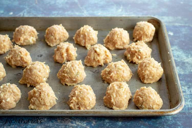 raw chicken meatballs on a baking sheet