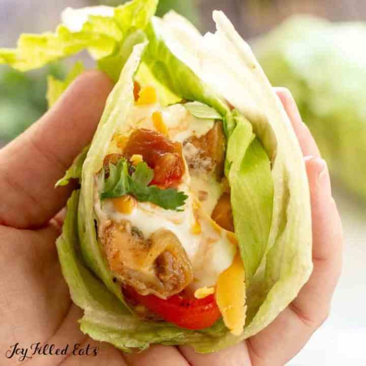 a hand holding a lettuce wrap fajita