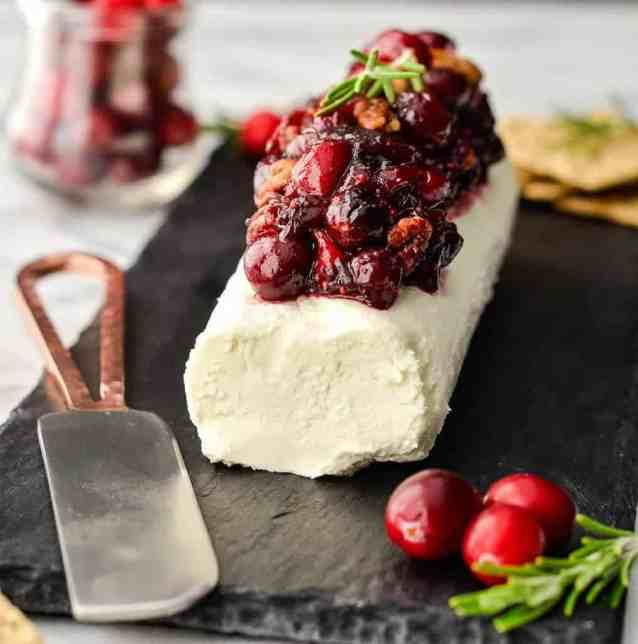 side view of Balsamic, Maple & Cranberry Goat Cheese Appetizer with Cinnamon Toasted Pecans before cutting