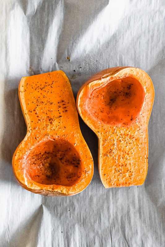 Two roasted butternut squash halves on a baking sheet