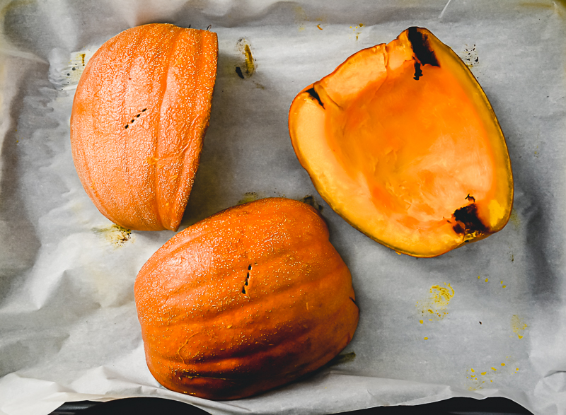 Three pieces of roasted pumpkin on a baking sheet