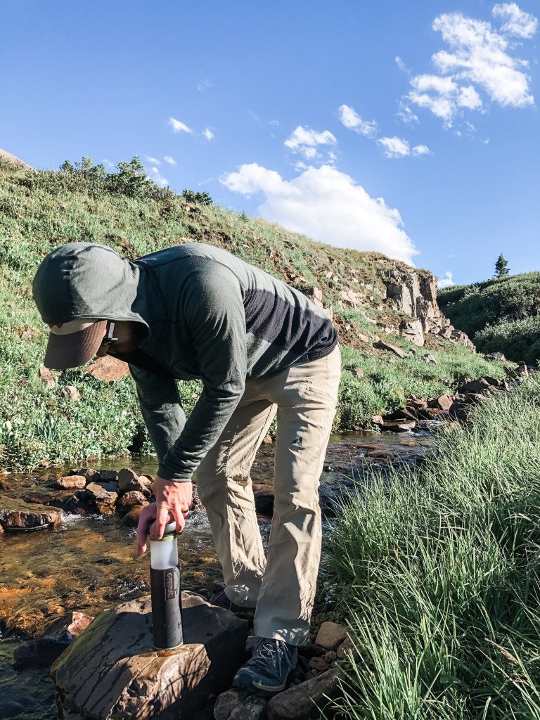 Filtering water through Grayl water bottle on backpacking trip in Colorado