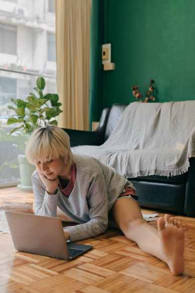 Woman using her laptop and stretching out her leg on her apartment floor. She is looking for the right online therapist in oakland, ca. The Joyful Empath offers online couples therapy in san francisco, ca, online couples therapy in california, online therapy in marin, ca, and more.