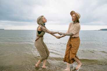 Women holding hands on the beach. They are happy to feel more connected after working with  an LGBT affirming therapist in San Francisco, CA. Joyful Empath offers LGBTQ therapy in Marin, CA, transgender therapy, LGBTQ therapy, and more.