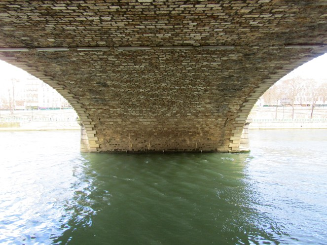 Walking under Marie Bridge, one of three bridges connecting Ile St Louis to the Right Bank.