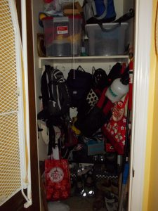 small closet crowded with sports gear