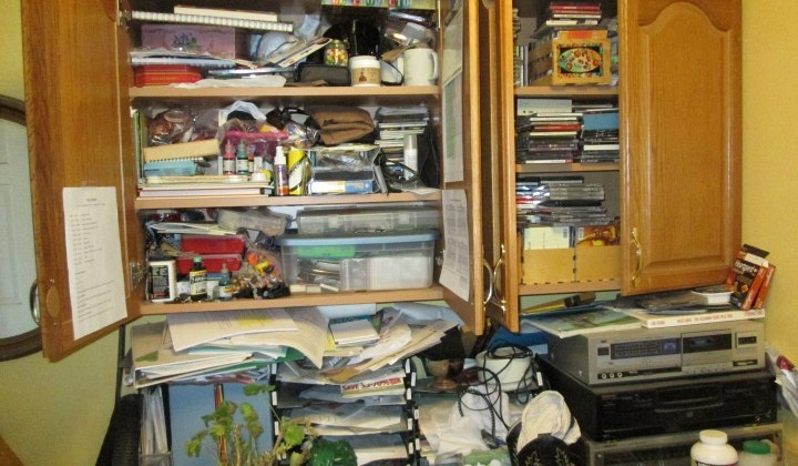 cluttered paperwork spilling out of a cupboard onto the counter