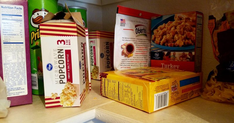 popcorn, snacks, taco shells and stuffing mix jumbled together on a pantry shelf