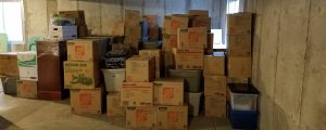 brown moving boxes stacked haphazardly in an poorly lit unfinished basement