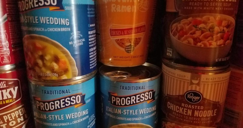 rows of canned soup on a pantry shelf