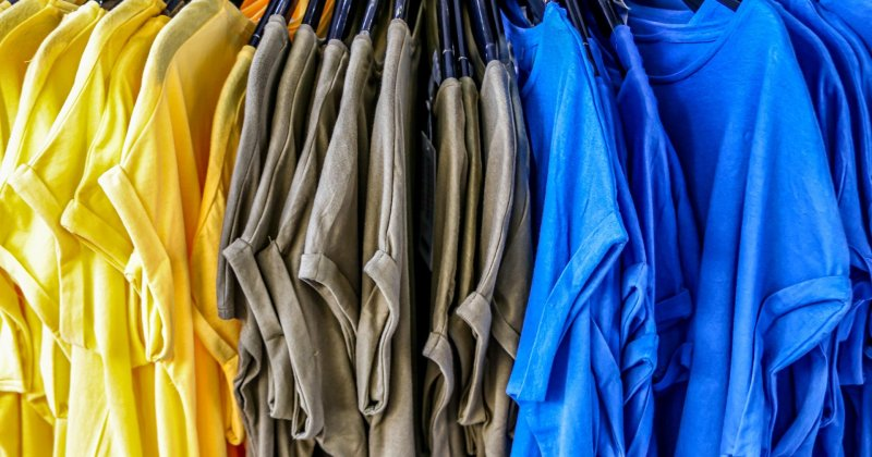 yellow gray blue t-shirts on hangers in an orderly row