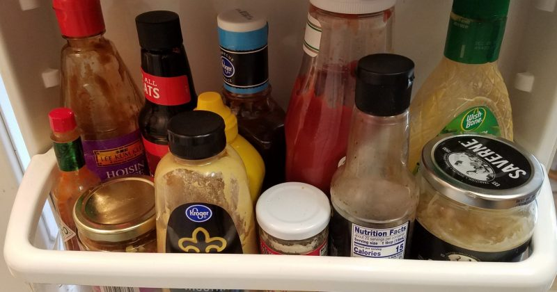 condiments crowded into a fridge door shelf