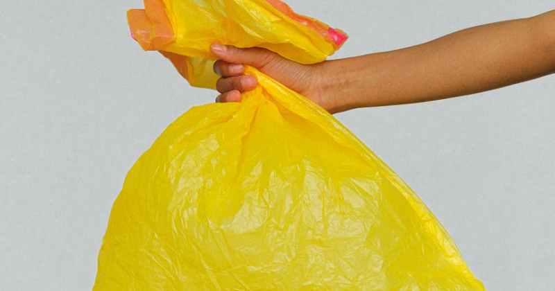 hands holding yellow plastic bag