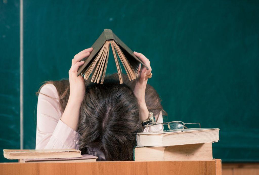 Teacher with head down on desk