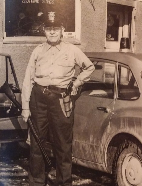 Dexter officer John Love, in front of his store
