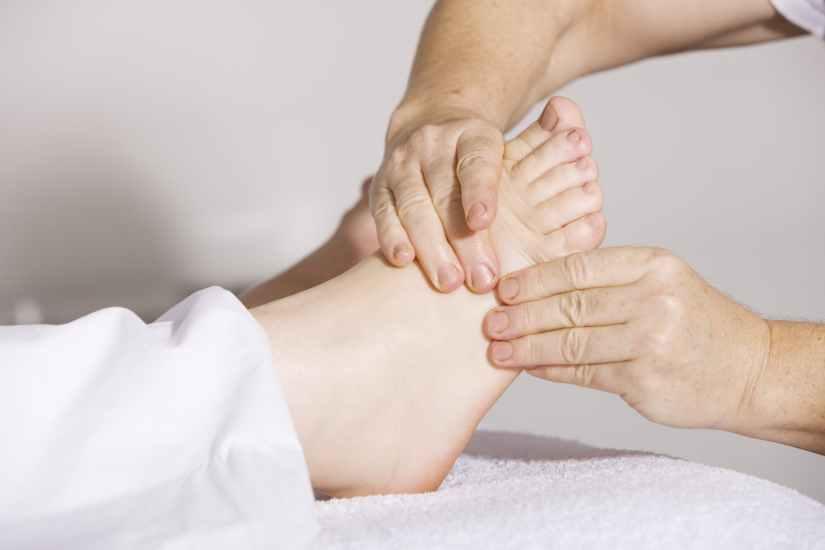 two hands massaging a foot