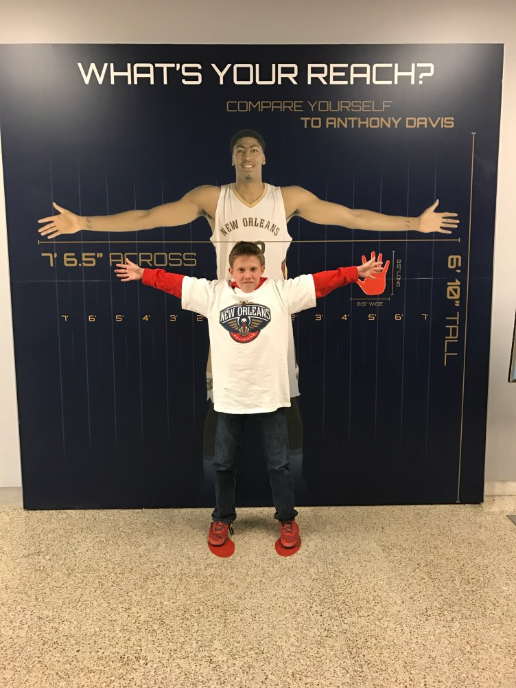 The words What's Your Reach? with NBA player Anthony Davis spreading his arms out wide and child standing in front