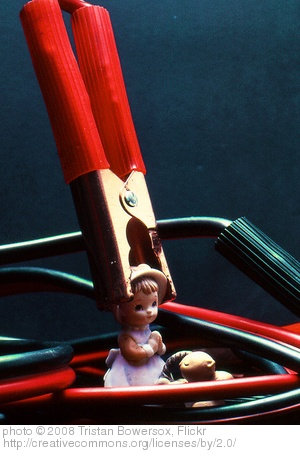 doll in the grip of a jumper cable