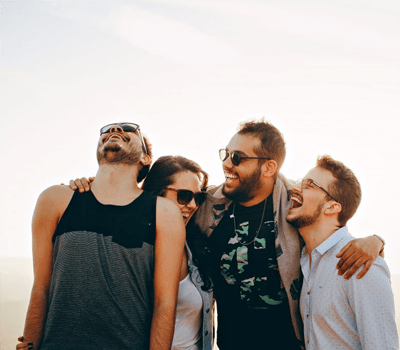 a group of four young adults are laughing outside
