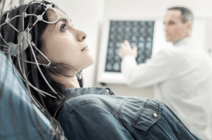 a woman running a brain test is staring at the ceiling as the doctor behind her looks at the results