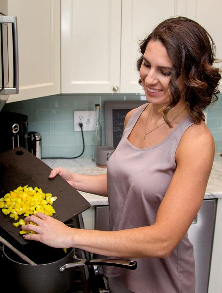 young woman preparing healthy food over the counter in her kitchen