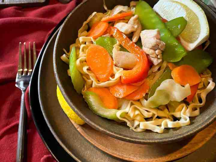 Egg noodles with carrots, shiitake mushroom, pea pods, onions, garlic, green onions, pork and chorizo topped with cilantro in a white ceramic bowl