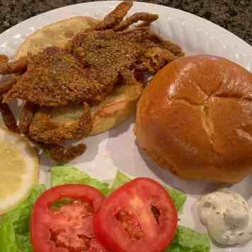 Soft shell crab sandwich on a brioche bun with lettuce and tomato with slice of lemon and tartar sauce served on a white plate