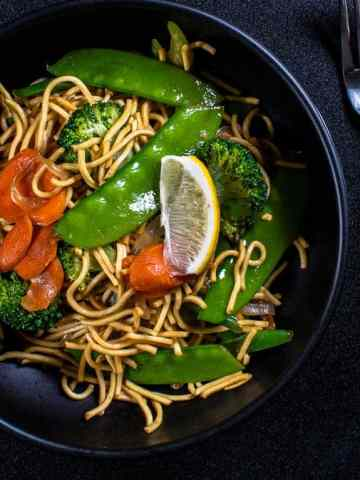 Filipino Vegetable Pancit in a black bowl with a fork