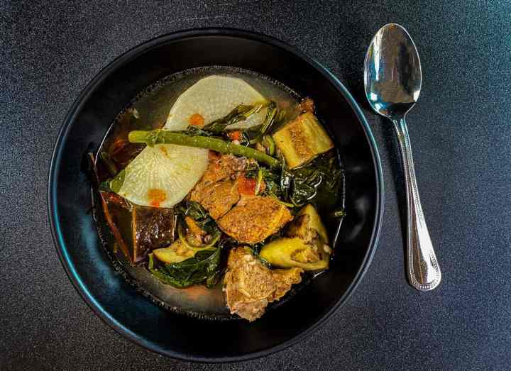 Sinigang Pork in black bowl with rutabaga, eggplant, spinach, green beans and tomatoes