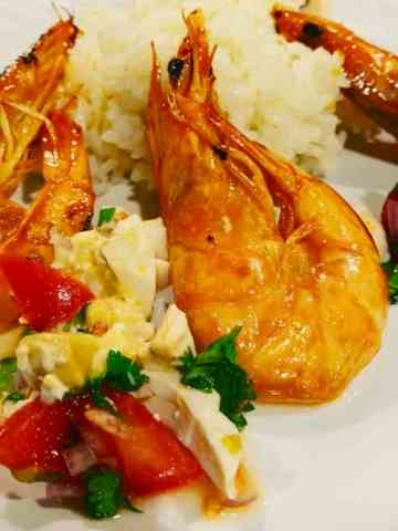 Caramelized shrimp on a bed of garlic rice with salted duck egg and tomato relish with cilantro on a white dish