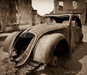 Carcasse d'une voiture sur la champ de foire du village